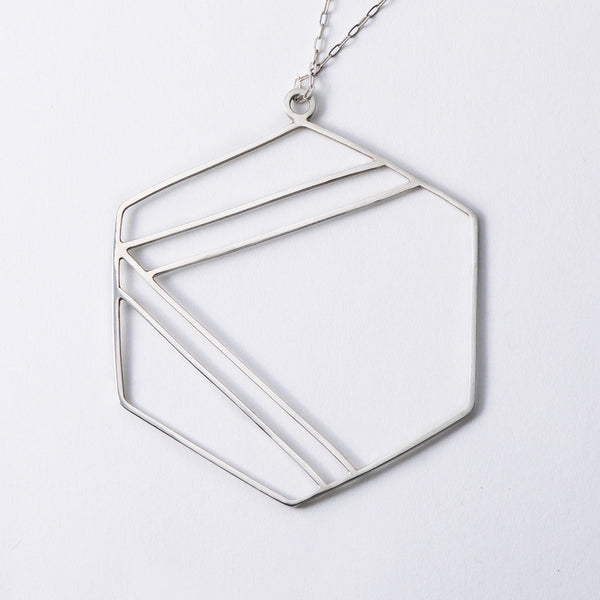 Sterling silver necklace with hexagonal shape outline and center geometric stripe design