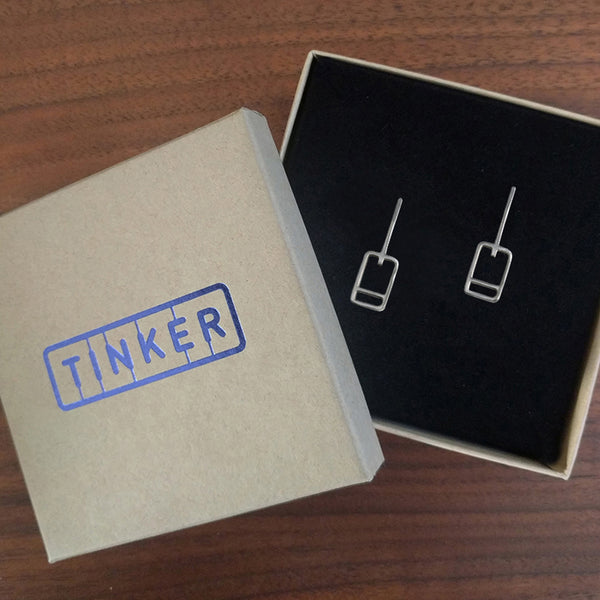 Modern minimal earrings, design inspired by lift tickets, made of recycled sterling silver. Shown here in a Tinker Company box.