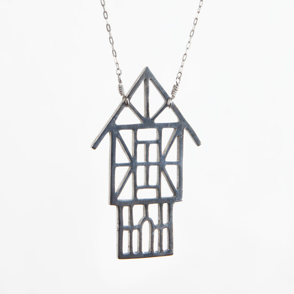 Angled view of the Tudor Ski Chalet Necklace in solid sterling silver. Architectural jewelry designed and made in NYC by Tinker Company.