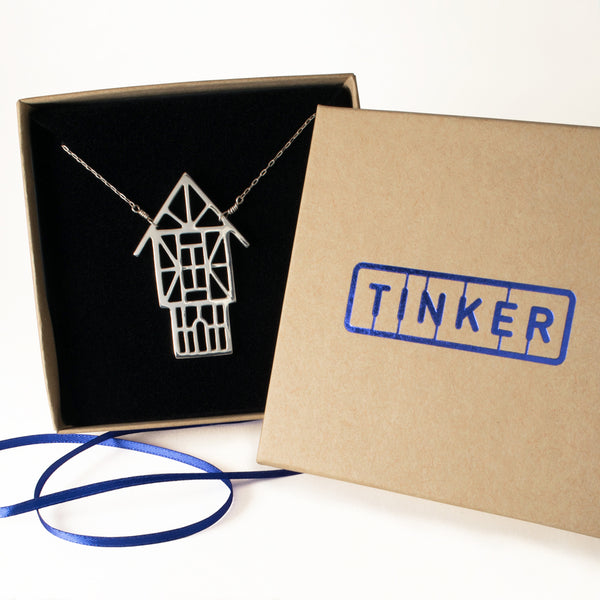 Tudor Ski Chalet Necklace shown in a Tinker box with blue ribbon. The perfect gift for your favorite skier or snowboarder.