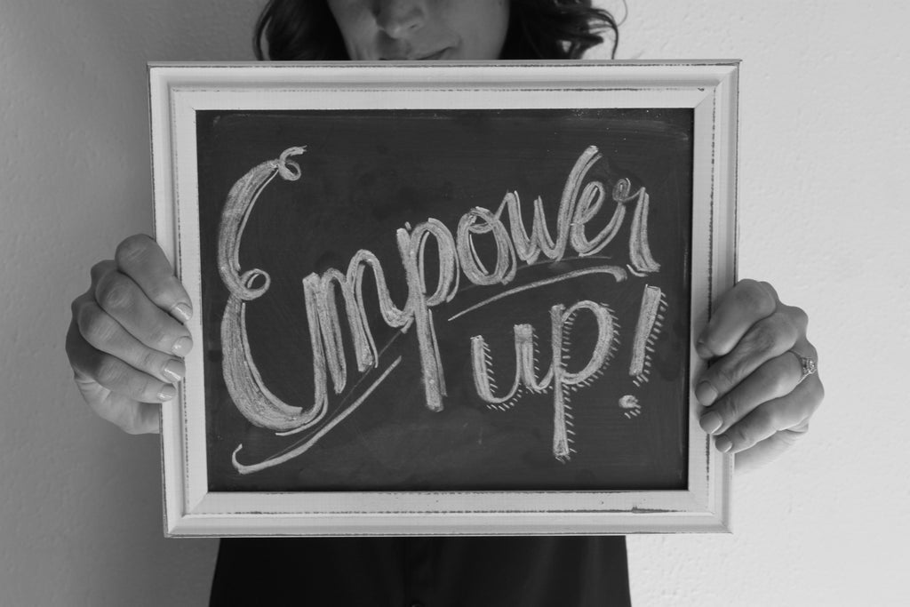 Stacy Davison, creator of the Personal Pep Talk strategy card decks, holding a chalkboard with a hand lettered message that says Empower up!