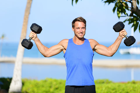 man lifting two dumbbells in a park