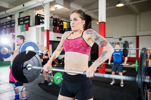 woman lifting a barbell in a gym