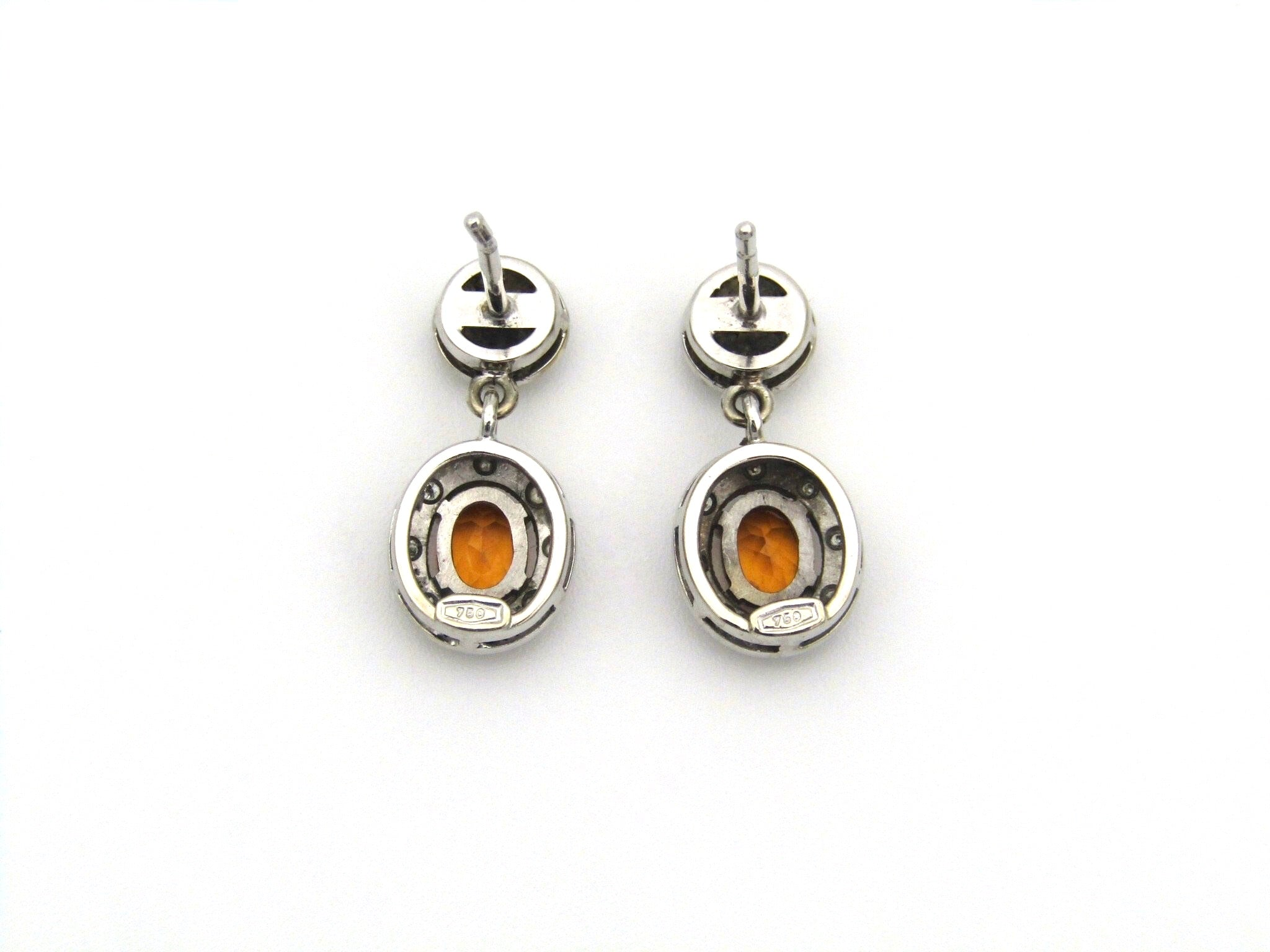 A pair of 18K gold diamond and spessartine garnet drop earrings.