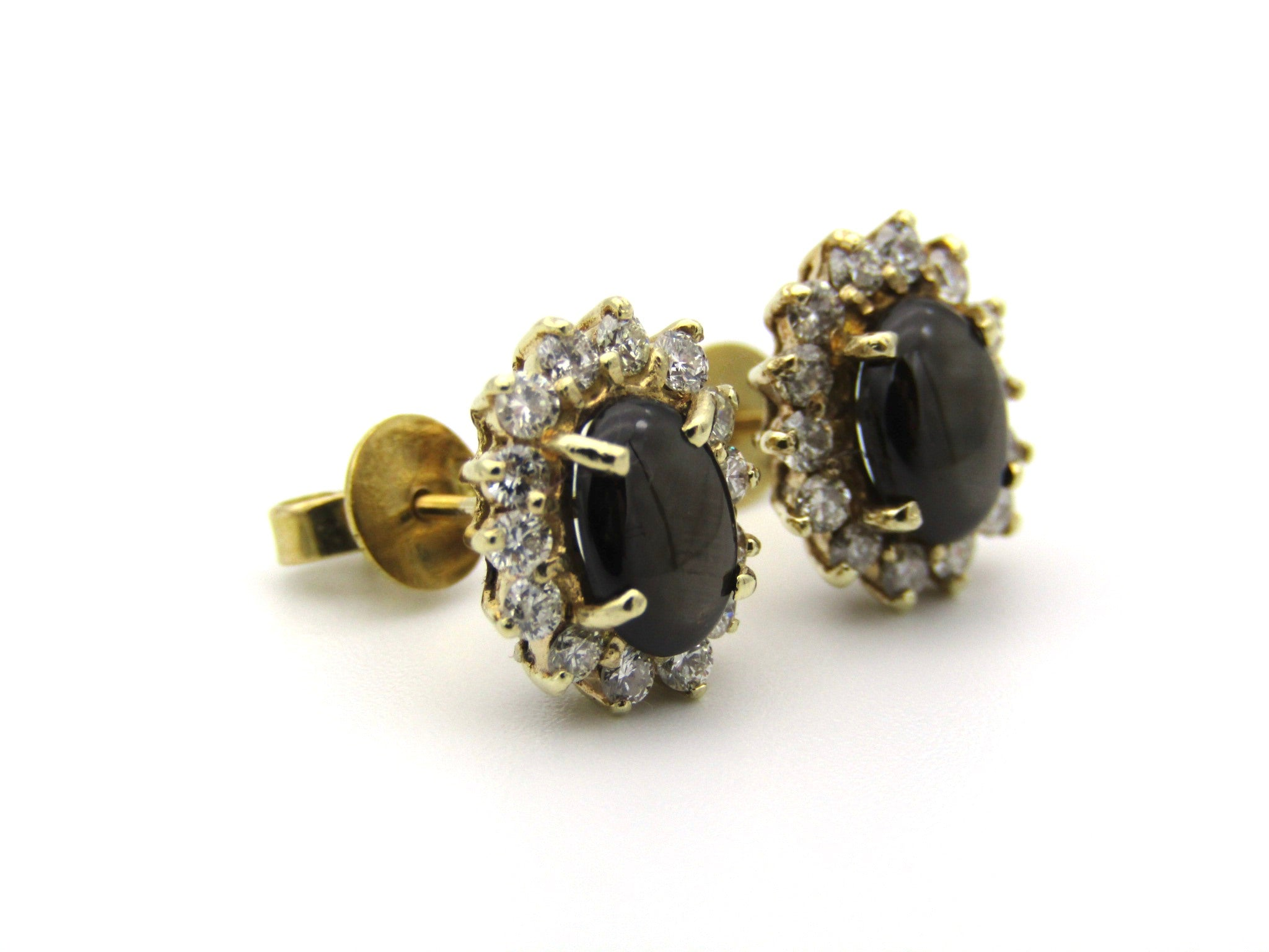 A pair of 18K gold black star sapphire and diamond earrings.
