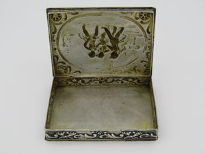 Continental silver table snuff box, stamped 800. The lid is embossed with scrolls and cherubs.