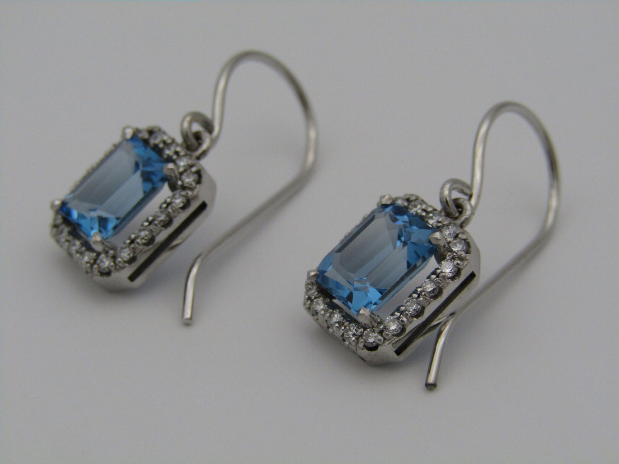A pair of 14kt gold blue topaz and diamond earrings.