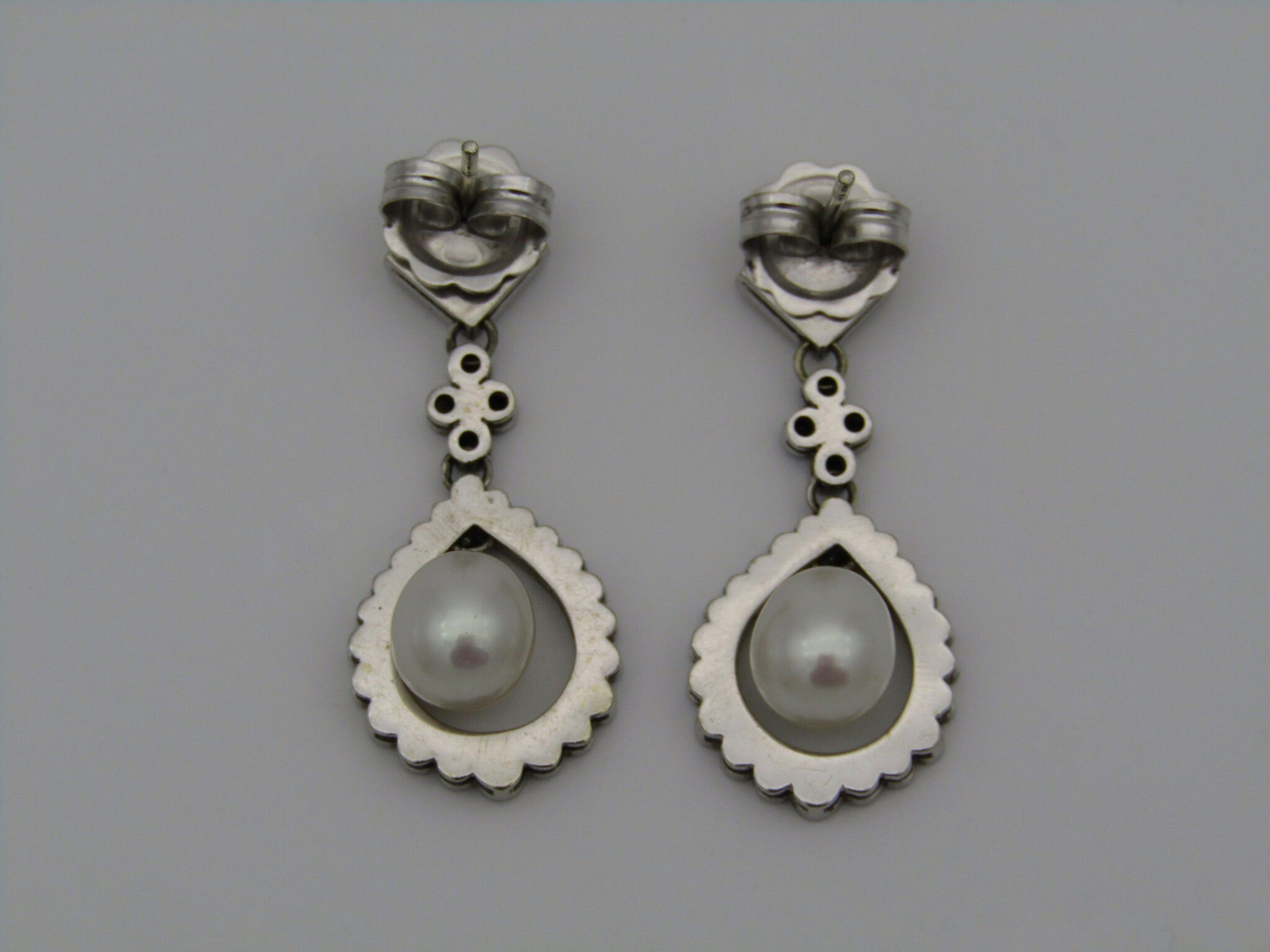 A pair of 9kt gold pearl and diamond earrings.