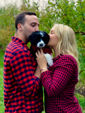 Are You Ready For a Puppy? | small black and white PWD puppy is being held in between two owners. They are all dressed in buffalo plaid and the owners are kissing her head. | Bubu Brands