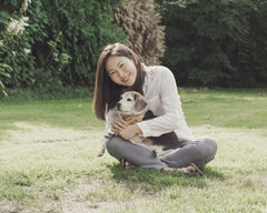 A girl holds her small beagle dog in her lap surrounded by green grass and trees. The girl is smiling at the camera while her dog looks off to the side.