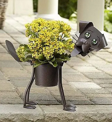 15 Perfect Gifts to get a Dog Lover | A dark colored dog shaped flower pot with small light colored flowers as the body | Bubu Brands