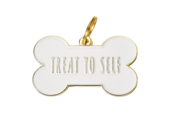 "A light colored dog tag that says ""Treat Yo Self"" 