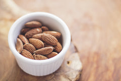 A bowl of almonds in a light colored bowl on a wood table | Bubu Brands