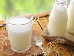 A glass of light colored milk with a spoon next to it and a glass jar of light colored milk | Bubu Brands