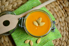 A glass jar with pumpkin paste on a bright colored napkin with pumpkin seeds in it and next to it | Bubu Brands