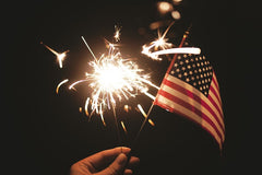A person holding a sparkler and an american flag | Bubu Brands