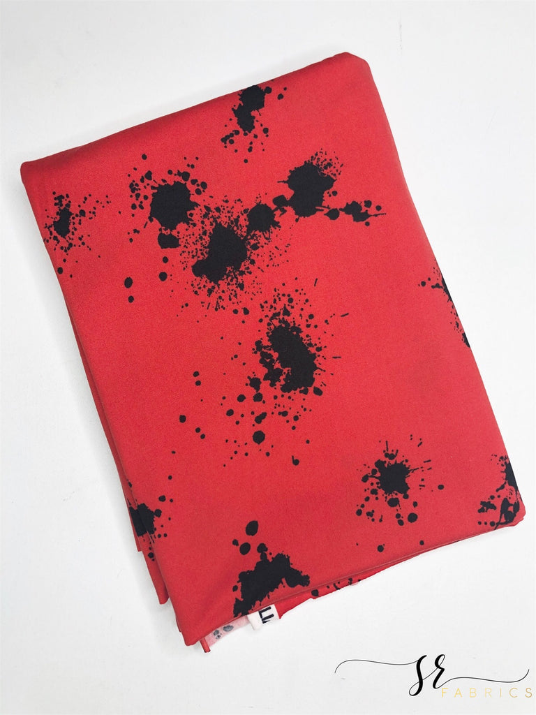 Red and black splattered paint brushed poly knit