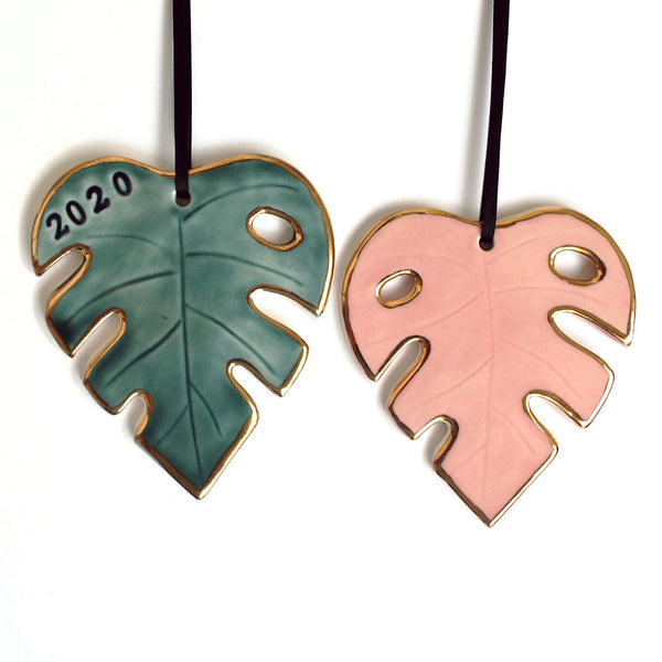 two monstera leaf shaped ornaments, in green and pink