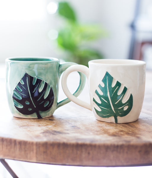 Two mugs, with a Monstera leaf carved on the side. Left shows a green mug with black leaf. Right mug has a green leaf and white mug.