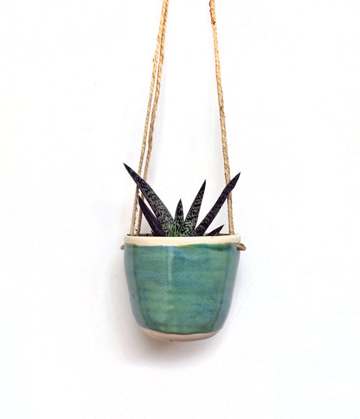 Hanging ceramic planter, with blue-green glaze, on a hemp string, with a succulent planted