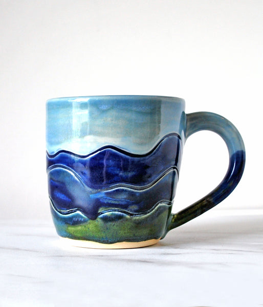 Ceramic Handmade Mug, with blue sky background and Blue Ridge Mountain design: blue and green mountain ranges