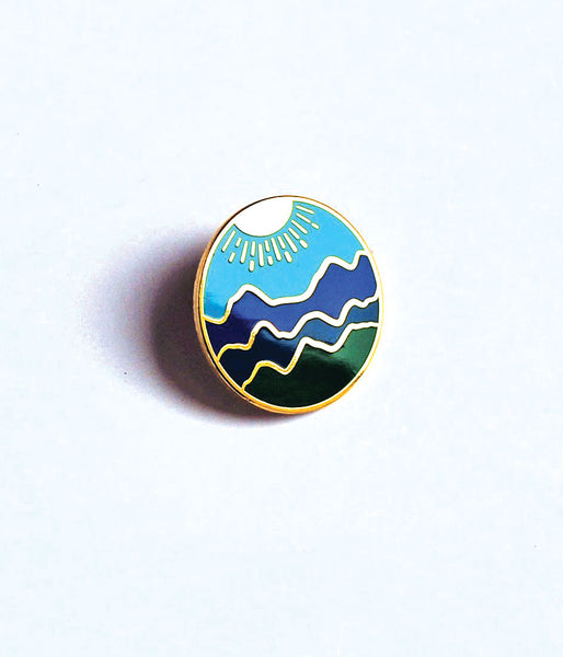 Enamel Pin with Blue Rige Mountain Design: blue sky background, gold sun, blue and green mountain ranges