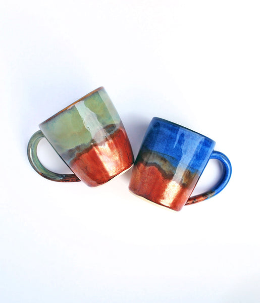 Ceramic coffee mugs with bronze glaze on the bottom half. Left mug has green on top half, right mug has blue on top half.