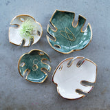 Green and white monstera leaf dishes with gold luster edges