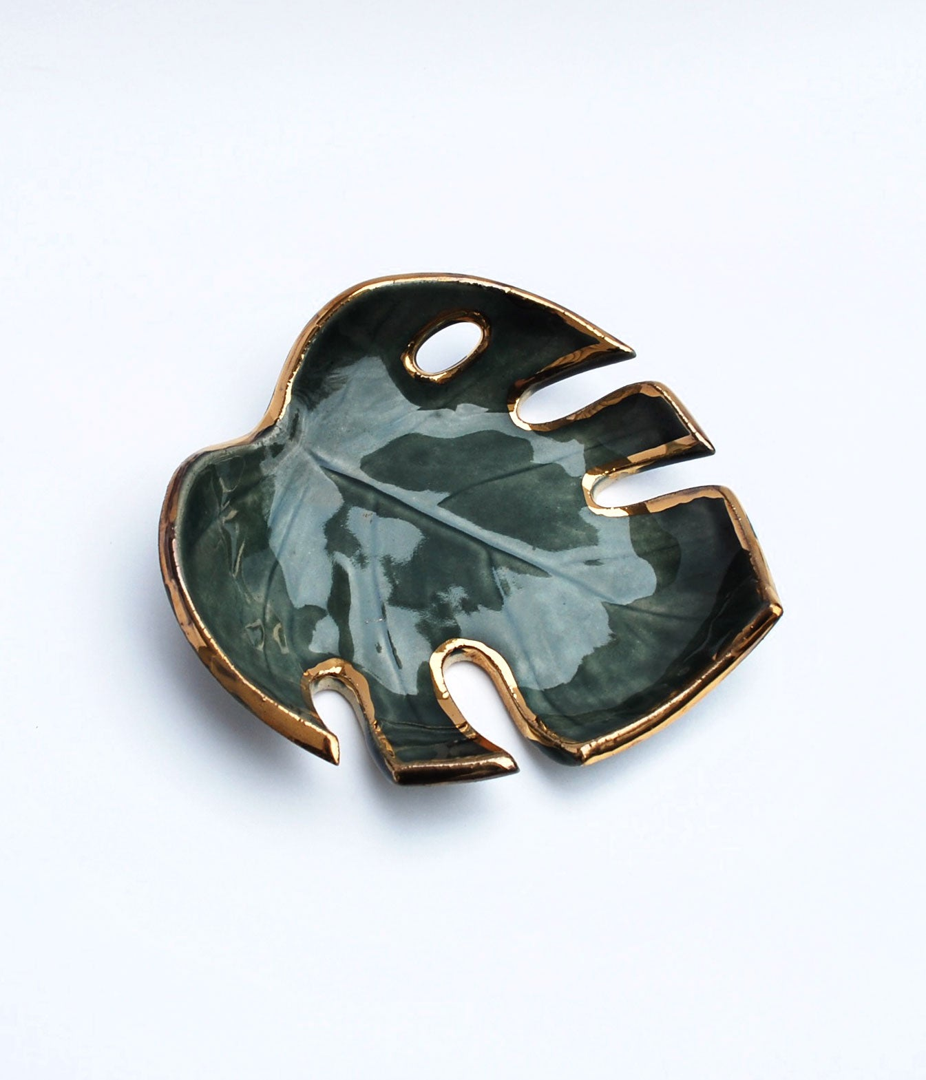 Dark green Monstera leaf bowl with gold luster on the edges