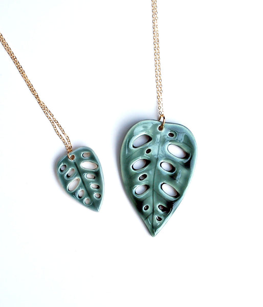 Two ceramic necklaces, small and large, in the shape of a Monstera Adansonii leaf. On a gold chain.