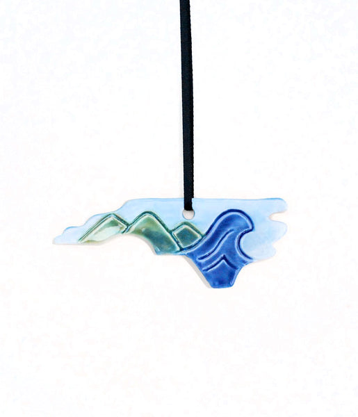 North Carolina shaped ornament with green mountains on the left and a blue ocean wave on the right.