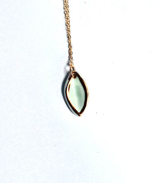 Aqua oval shaped necklace with gold luster outline, on a gold chain.