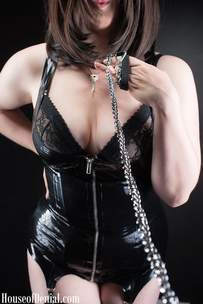 Mistress K wearing a latex corselette holding a metal leash