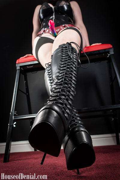 Mistress K wearing a latex corset dress and leather knee high boots