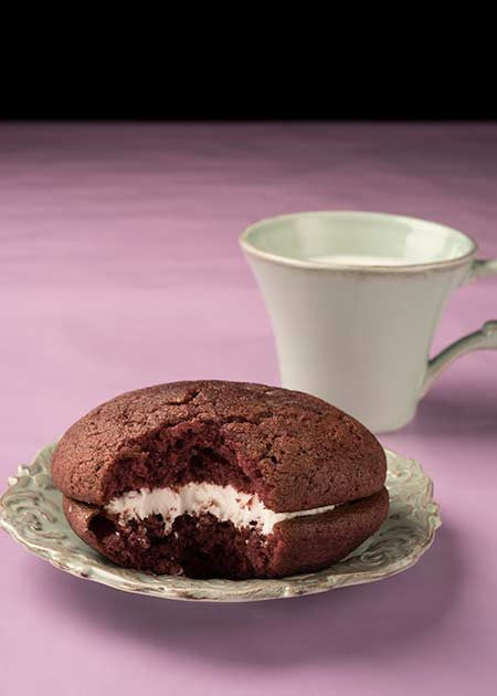 Black raspberry whoopie pie on a plate with a bite taken out.