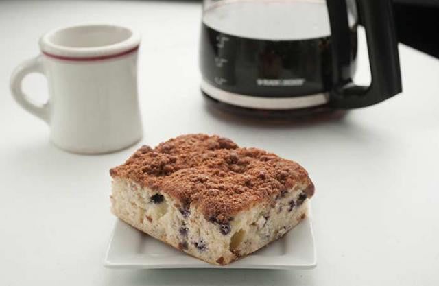 a square of Blueberry coffee cake with coffee in the background