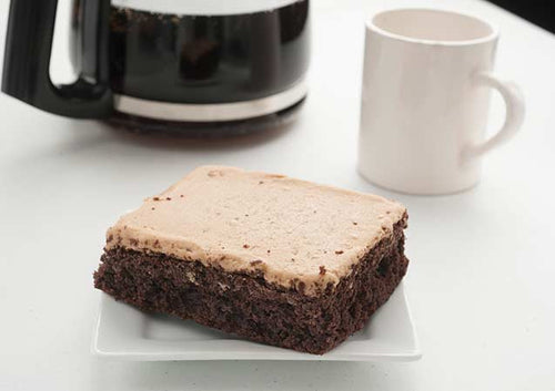 chocolate cake square with peanut butter frosting on a plate with coffee