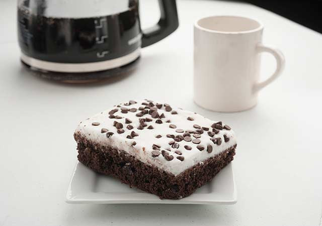 frosted chocolate cake square with mini chips and coffee