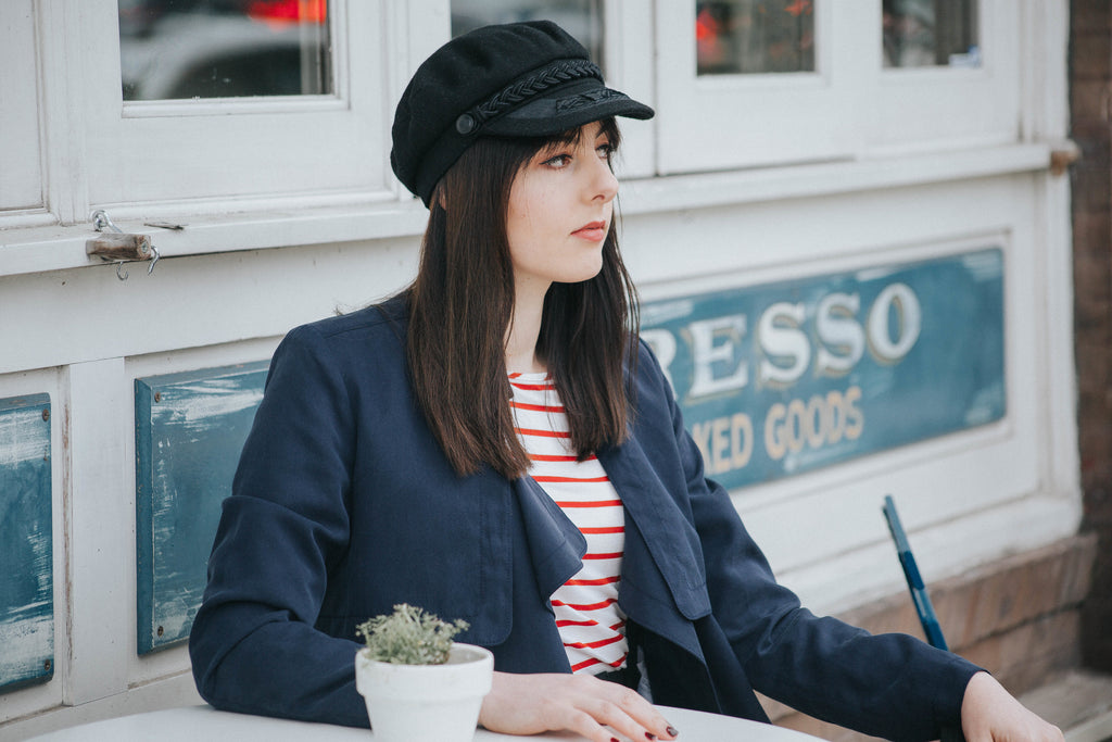 Lindsey wearing a vegan Free People sailor hat, striped Amour Vert top, and Banana Republic trench coat