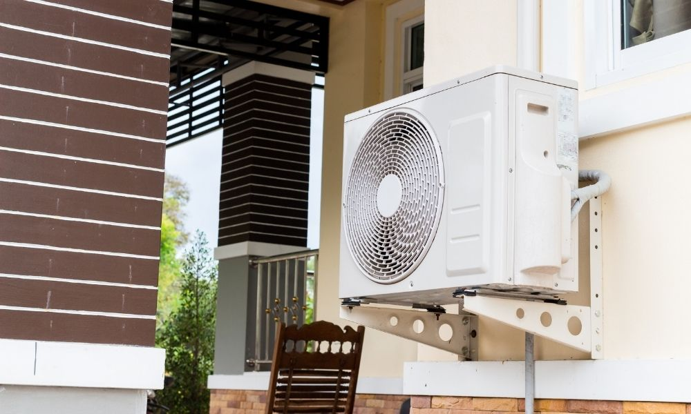 <p>Heat pumps are usually used in milder climates, where winter exists but temperatures aren't as harsh as northern climates. A heat pump needs protection so it functions well and keeps the house warm. Understanding <strong>how to protect your outdoor heating pump </strong>is essential to have an efficient heating system. </p><h2>Build a Roof</h2><p>Snowfall is a problem for heat pumps. Remove snow when it piles up around and on top of the heat pump.</p><p>However, we don't recommend completely covering it. The pump works by bringing in external air, heating it, then pumping it into your house. If you cover it, the pump won't be able to suck in air. </p><p>Instead, build a roof over the heat pump. Keep in mind a heat pump needs 18-24 inches of space all around so it can do its job properly. When a roof is built correctly and leaves enough space for the pump, it can alleviate snow issues. </p><h2>Check the Defrost Cycle</h2><p>Heat pumps have a defrost cycle to keep ice from forming. If you stay on top of yearly maintenance checks with your HVAC professional, your defrost cycle will work well. If you notice ice buildup in the winter, call your service. Ice buildup on a heat pump is damaging and eventually causes the pump to stop working. </p><h2>Create a Wind Barrier</h2><p>Creating a wind barrier helps the heat pump run efficiently. Wind causes the following issues:</p><ul><li>Less fan efficiency</li><li>Less fan reliability</li><li>Fan damage </li><li>Ice accumulation </li><li>Unstable indoor temperatures</li></ul><p>Create wind barriers by planting hedges and shrubs in front of the pump. Keep your barrier 18-24 inches away from the heat pump for greater efficiency. </p><h2>Off the Ground</h2><p>Elevate your heat pump to avoid contact with snowfall and heavy rains. Elevation also helps with proper drainage of the heat pump. </p><p>Raise a heat pump at least six inches off the ground (or higher if heavy snowfall is predicted.) You can do this using risers or concret