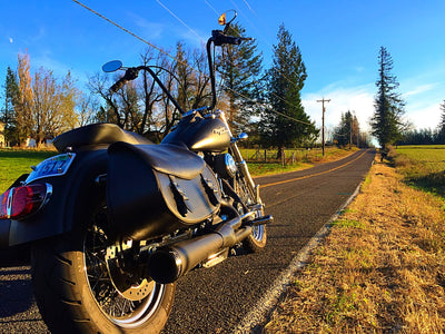 Harley Davidson with US Saddlebag's signature classic black leather motorcycle saddlebags, parked on the open road.