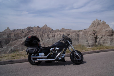 Honda VTX 1300C with black paint job and customized with US Saddlebag's signature classic black leather saddlebags. Parked with mountains in the background.