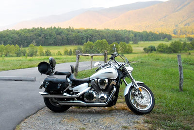 Honda VTX 1300C with Black Leather Motorcycle Saddlebags and Embossed Inlay pattern. Parked with mountain in background.