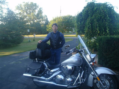 Studded Black Leather Motorcycle Saddlebags mounted to a 2008 Silver Honda VTX 1300R - customer standing next to bike