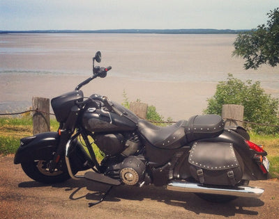 Studded Black Leather Motorcycle Saddlebags mounted to 2017 Black Indian Dark Horse parked with water in background