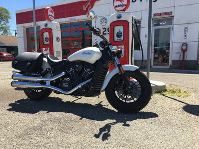 Pearl white Indian Scout with our Classic Black Leather Motorcycle Saddlebags. The bike is parked at an old looking gas station.