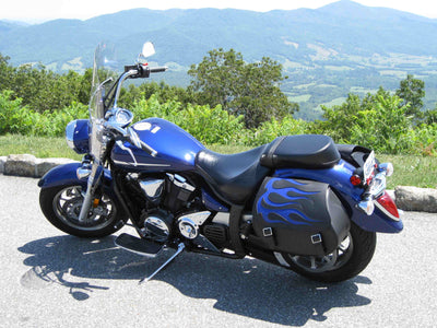 Yamaha Vstar with black motorcycle saddlebags customized with a blue flame leather inlay. Mountains in background!