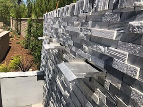 Brushed Stainless Steel Waterfall Spillway Fountain Scupper on Gray Stacked Stone