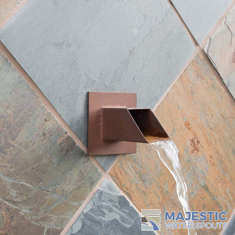 Square 2 inch water spout shown in pool fountain wall outdoors
