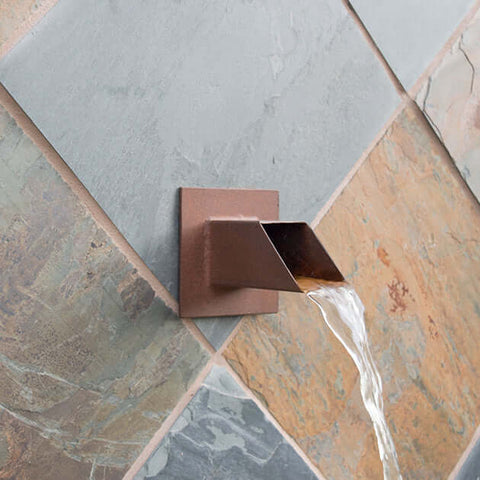 Square 2 inch brown water spout mask in wall of pool outdoors